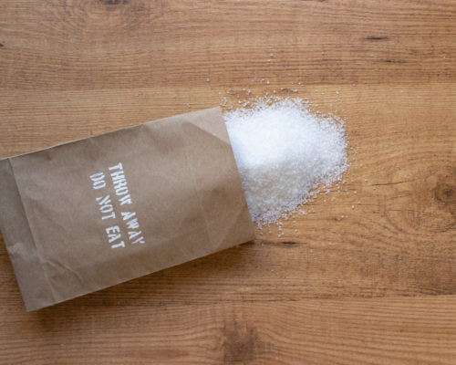 "Salt in the paper pack on the table. ""Throw away, do not eat"" added salt intake health warning on the packet."