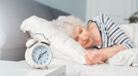 Grandma sleeping in bedroom. Deep sleep. Can not hear alarm clock. Indoor, studio shoot, bedroom interior