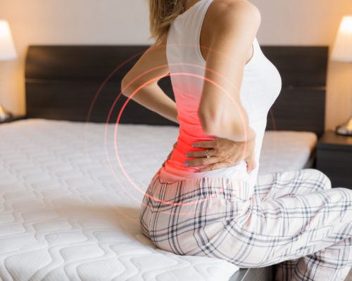 Caucasian ethnicity female suffering from back pain because of uncomfortable mattress
