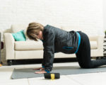 Active elderly female learning cow pose online through smartphone at home