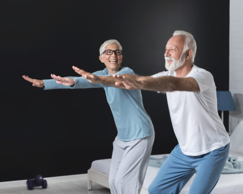 Portrait of happy senior couple performing exercise at home. Two positive couple full of energy and optimism in old age. Copy space image