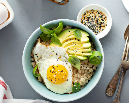 Savory oatmeal with sunny side up egg and avocado for breakfast overhead