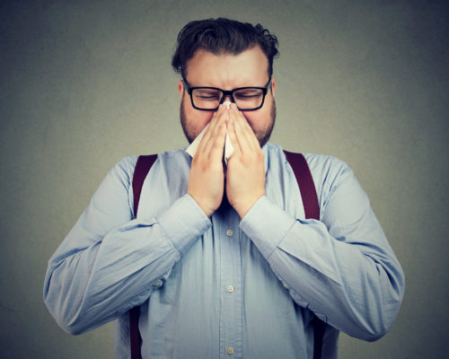 Young chubby man suffering from flu blowing his nose using napkin.