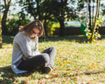 Sad young woman suffering from period pain sitting down outdoors - Beautiful girl with brown hair wearing jeans having menstruation cramps while holding her belly in the park