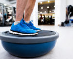 Close up of legs of senior man in gym standing on bosu balance ball and exercising as part of bodybuilding training