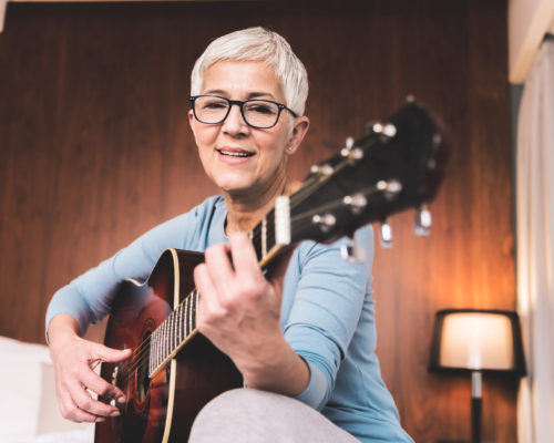Portrait of beautiful mature woman playing guitar in cosy modern apartment, Free time hobbies music and art concept