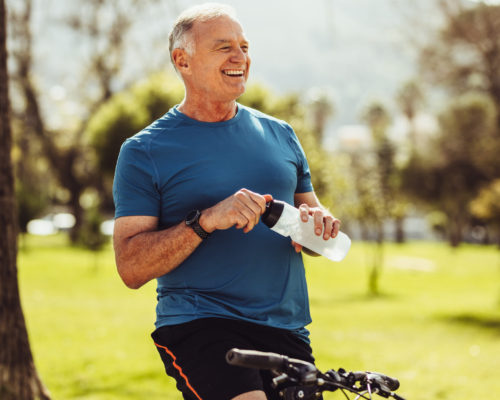Senior man in fitness wear drinking water sitting on his bicycle. Cheerful senior fitness person taking a break during cycling in a park.