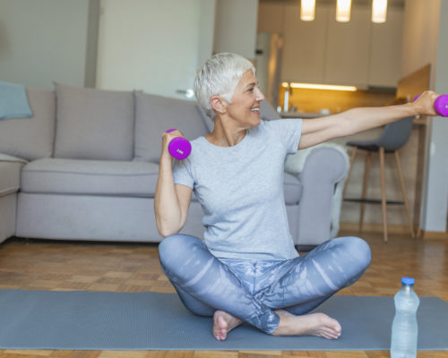 Senior woman lifting weights and working out at home. Mature woman sitting on couch doing hand stretching exercise using light weight dumbbells. Beautiful old lady exercising at home to stay fit.