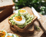 Healhy Breakfast Toast With Avocado, Boiled Egg On Wooden Cutting Board