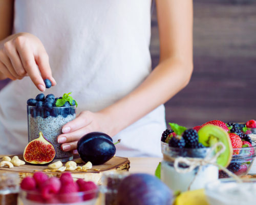 Female hands are preparing yogurt with chia and blueberries for good digestion, functioning of gastrointestinal tract. Summer berries, nuts, fruits, dairy products on table. Healthy food concept.