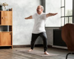 Senior hispanic man standing in warrior two yoga pose practicing in living room alone