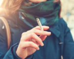 Young woman enjoying a cigarette outdoors holding it between her fingers, low angle view against the chest of a warm autumn jacket in a smoking and tobacco concept