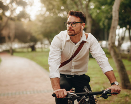 Man enjoying music using earphones while commuting to office on a bicycle. Businessman biking to office while listening to music.