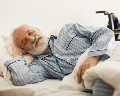 Older sick man with a oxygen mask lying in a hospital bed
