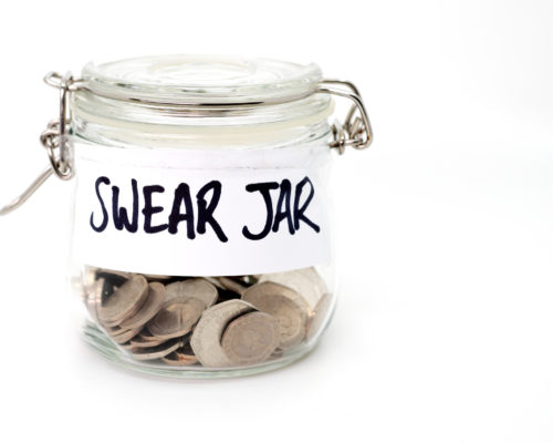 Swear jar with coins in on a white background
