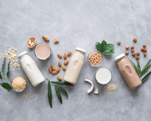 Various vegan plant based milk and ingredients, top view, copy space. Dairy free milk substitute drink, healthy eating.