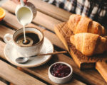 Pouring cream into cup of black coffee. Tasty breakfast table set with croissants, jam and coffee