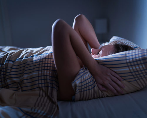 Sleepless lady covering ears with pillow. Noisy neighbors, tinnitus, insomnia or stress concept. Tired woman can't sleep. Awake in bed in the middle of the night. Noise from party next door.