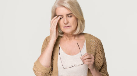 Upset tired old mature woman taking off glasses feeling eyestrain pain, stressed aged senior lady suffer from headache bad vision eye strain fatigue problem isolated on grey white studio background