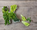 Vitamin K in food concept. Plate in the shape of the letter K with different fresh leafy green vegetables, lettuce, herbs on wooden background. Flat lay or top view.