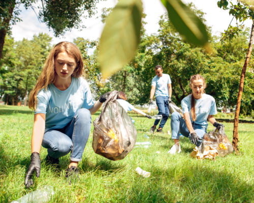 Young people girls volunteers outdoors helping nature girl close-up picking litter concentrated