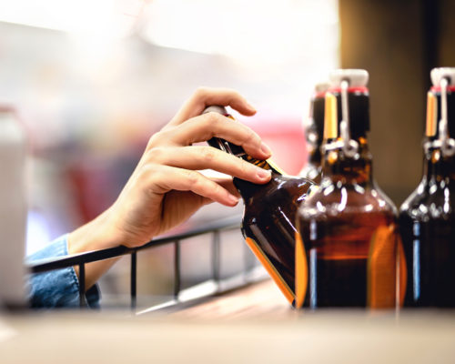Hand taking bottle of beer from shelf in alcohol and liquor store. Customer buying cider or supermarket staff filling and stocking shelves. Retail worker working. Woman choosing lager or pale ale