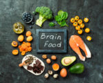 Brain food concept with copy space in center. Various food ingredients for thought and chalkboard with Brain Food letters over dark background. Top view or flat lay