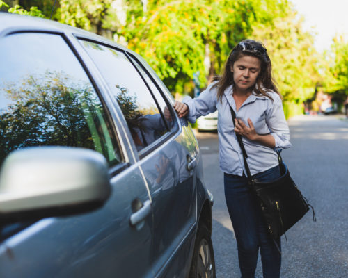 Weak young woman having chest pain while leaning against a car outdoors - Casually dressed female worker feeling tired while having breathing and respiratory problems on the street