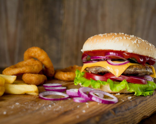Cheeseburger, french fries and onion rings on wooden chopping board over wooden backdrop. Horizontal, closeup view
