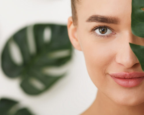 Woman with natural make up and green leaf over background, covering half of face