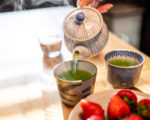 Woman hand holding teapot pouring hot traditional Japanese sencha green tea into cup with dessert strawberries on plate on at wooden kitchen table with steam