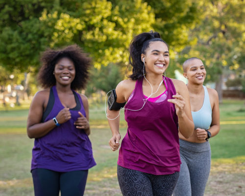 Group of curvy girls friends jogging together at park. Beautiful smiling young women running at the park on a sunny day. Female runners listening to music while jogging.