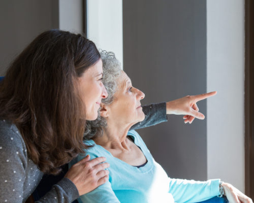 Adult daughter visiting elderly mother. Young woman showing to senior lady scene out of window. Dementia concept