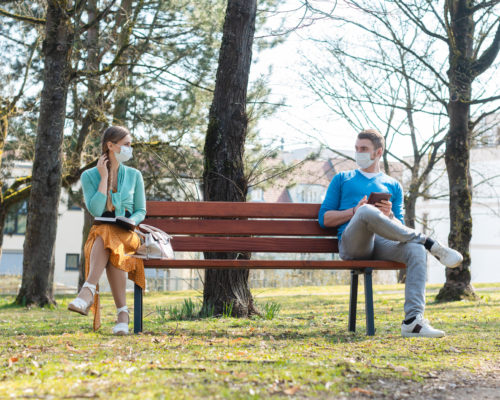Woman and man with face mask in social distancing flirting sitting on a park bench