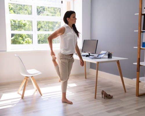 Young Businesswoman Looking At Folders On Shelf Doing Yoga