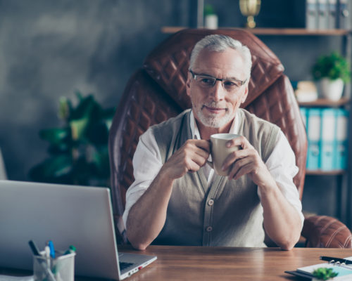 Cheerful careless excited joyful old businessman with bristle is pondering about holidays sitting on the armchair in front of laptop