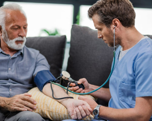 Doctor measuring blood pressure of a senior man while being in a home visit.