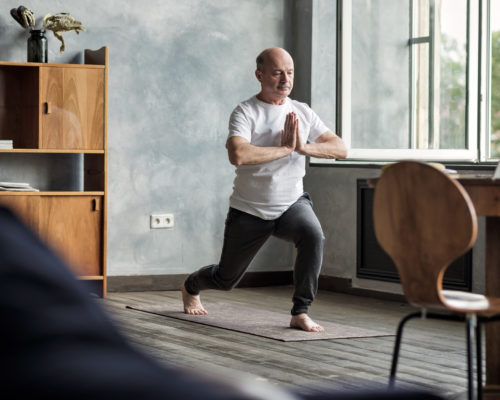 Senior hispanic man standing in warrior yoga pose variation practicing in living room alone