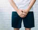 man wearing shorts holding genitals. Men's health, venereologist, sexual disease