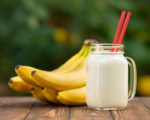 banana smoothie in mason jar on wooden table with green blurred natural background