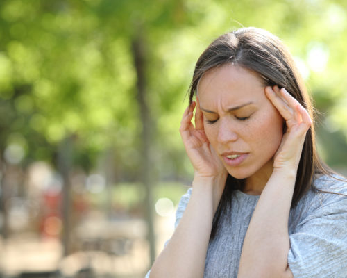 Woman suffering migraine outdoors in a park