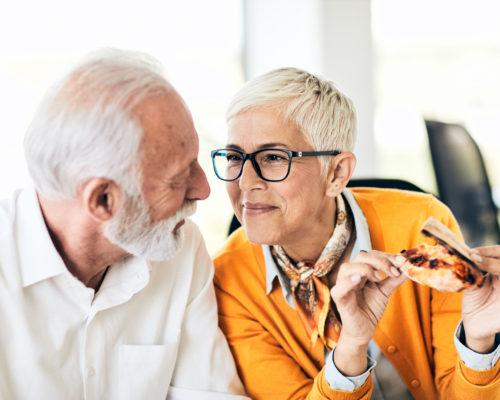 portrait of senior couple eating pizza