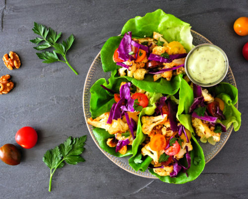Healthy lettuce wraps with grilled cauliflower, cabbage and tomatoes. Top view over a dark slate background. Plant-based diet concept.
