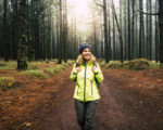 Happy hiker caucasian woman smile and enjoy the nature walking in a forest with high trees - alternative outdoor leisure activity and vacation lifestyle - sun in backlight and mist concept