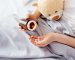Child taking medicines pills. Sick eight years boy lying in bed