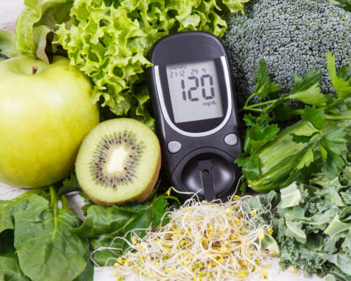 Glucometer for measuring sugar level and vegetables with sprouts as healthy nutritious food during diabetes containing vitamins and minerals