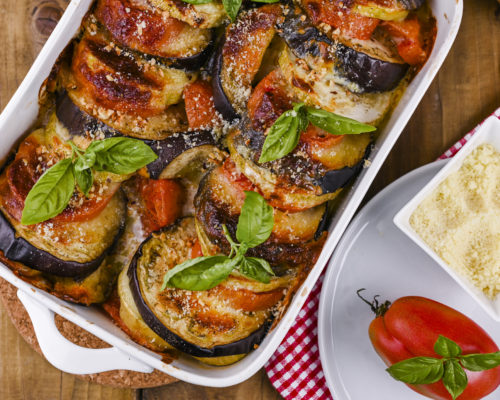 Traditional italian food. Baked eggplant, tomatoes with sauce, parmesan and basil. Rustic food for a healthy diet. Vegetables for lunch
