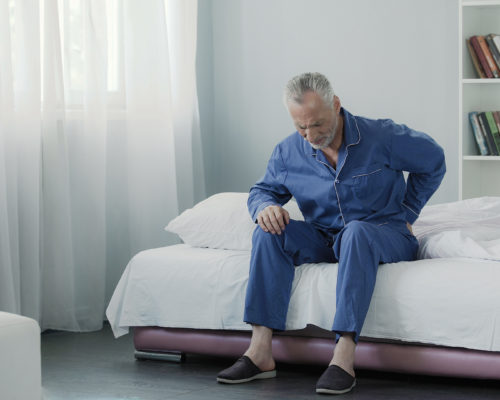 Retired man sitting in bed and feeling terrible pain in back, health and illness, stock footage