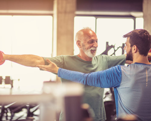 Fitness instructor helping senior man in exercise.