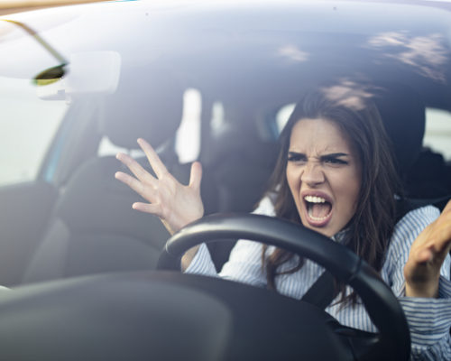 Closeup portrait, angry young sitting woman pissed off by drivers in front of her and gesturing with hands. Road rage traffic jam concept. Woman is driving her car very aggressive and gives gesture with his fist